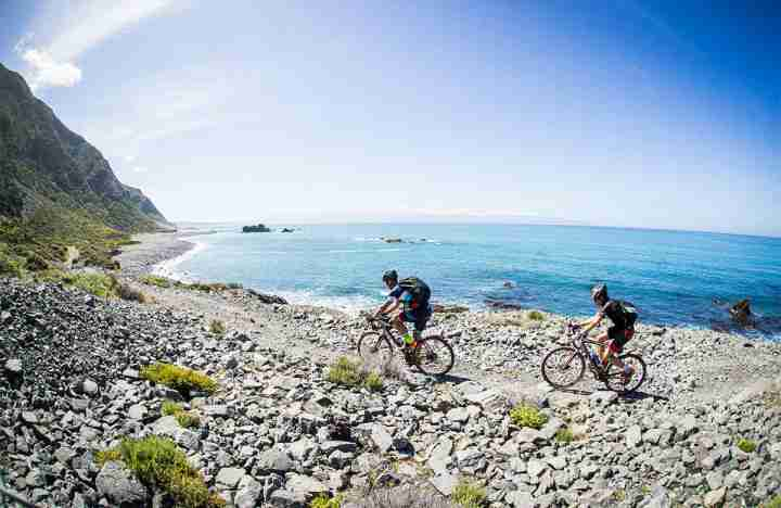 Remutaka Cycle Trail riders along rocky section of wild coast