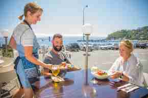 days bay seaside dining two people being served meal outside in sun