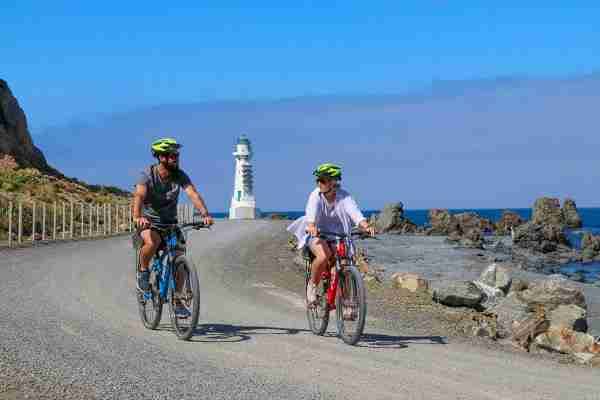 remutaka cycle trail pencarrow lighthouse two riders along coast